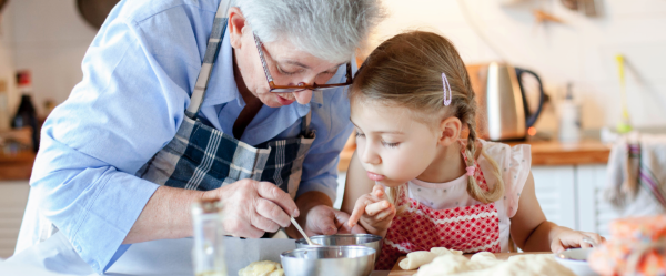 A grandma making cookies with her granddaughter.