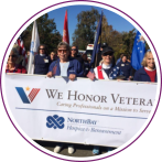 Hospice & Bereavement volunteers marching on Veterans day, holding a 'We Honor Veterans' banner. Some volunteers are carrying flags.