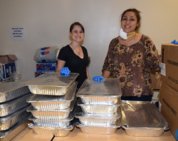 Volunteers smile as they prepare food for delivery