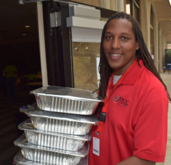 A volunteer with the Kroc Center carries trays of food donated by NorthBay healthcare into the SCC cafe.