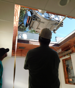 A crane drops the new MIR magnet through the roof of the modular building at VacaValley Hospital.