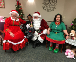 Santa Claus and company pose for a photo with one of the children at the party.