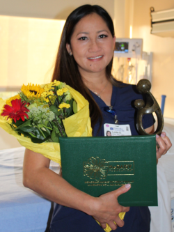 Loida De Vera, R.N., poses with her flowers, certificate and sculpture.