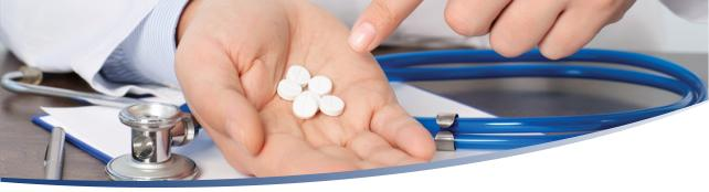 Image shows the open hand of a physician holding Warfarin (Coumadin) tablets. The doctor's hand is over a blue clip board and stethoscope.